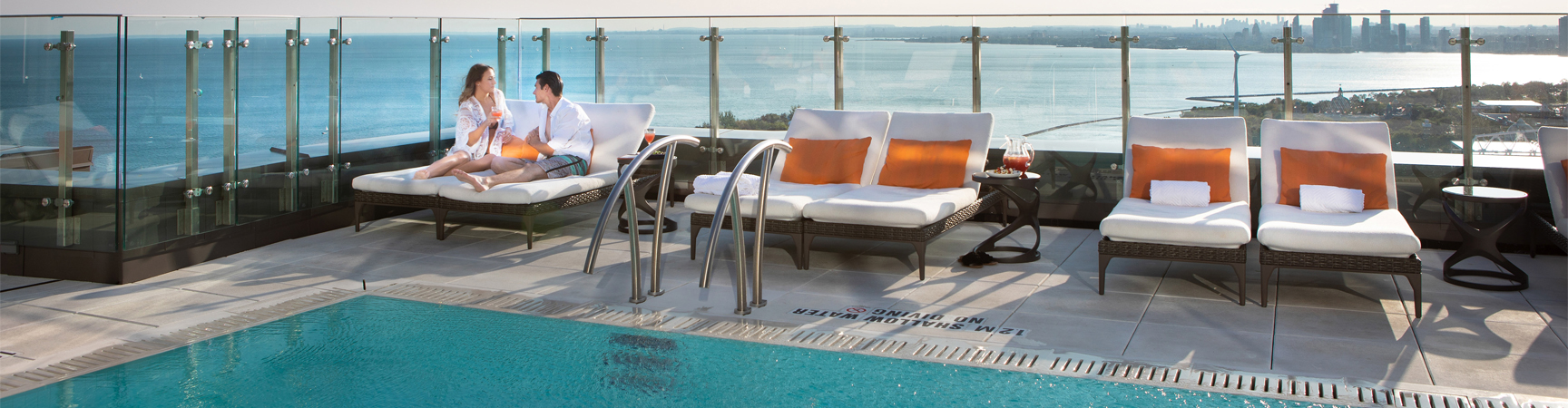 Man and woman sitting by the rooftop pool
